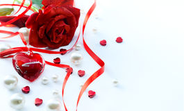 La tarjeta de felicitación de las tarjetas del día de San Valentín con los pétalos de rosas rojas y la joyería oyen Imagen de archivo