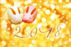 la tarjeta de felicitación de 2018 japoneses con el conejo formó los pasteles y el fondo del oro Fotos de archivo
