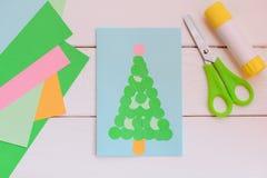 La tarjeta de felicitación de papel con el árbol de navidad, papel coloreado cubre, las tijeras, palillo del pegamento en una tab Fotografía de archivo libre de regalías
