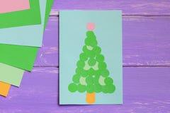 La tarjeta de felicitación de papel con el árbol de navidad verde, papel coloreado cubre en una tabla de madera púrpura Idea simp Imagenes de archivo