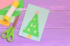 La tarjeta de felicitación de papel de la Navidad, las hojas del papel coloreado fijó, las tijeras, palillo del pegamento en una  Imagenes de archivo