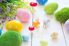 La tarjeta de felicitación de Pascua con las flores, conejito de los conejos de pascua juega y eggs en el tablón de madera blanco Fotos de archivo
