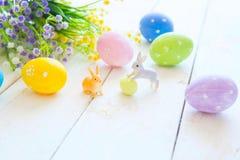 La tarjeta de felicitación de Pascua con las flores, conejito de los conejos de pascua juega y eggs en el tablón de madera blanco Imagen de archivo