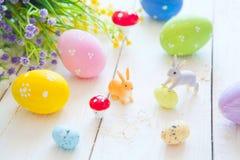La tarjeta de felicitación de Pascua con las flores, conejito de los conejos de pascua juega y eggs en el tablón de madera blanco Fotografía de archivo