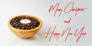 La tarjeta de la Feliz Navidad y de la Feliz Año Nuevo con la vela se enciende en una taza de madera con los granos de café para  Fotos de archivo libres de regalías