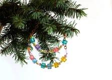 La tarjeta de la Feliz Año Nuevo y de la Feliz Navidad goteó la guirnalda de la letra en brunch del árbol de abeto Fotografía de archivo libre de regalías