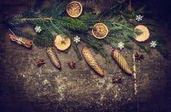 La tarjeta de Navidad con el abeto ramifica con los conos en fondo de madera rústico oscuro Imagen de archivo libre de regalías