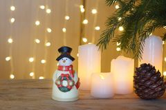 La tarjeta de Navidad con la guirnalda festiva, un muñeco de nieve se coloca en una tabla de madera Foto de archivo