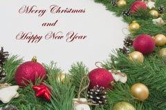 La tarjeta de Navidad del saludo con la guirnalda del pino natural ramifica, las bolas, espacio de la copia del mandarín Fotografía de archivo