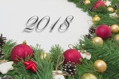 La tarjeta de Navidad del saludo con la guirnalda del pino natural ramifica, las bolas, espacio de la copia del mandarín Fotos de archivo