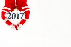 La tarjeta de Navidad, guantes en las manos que sostienen nieve registra con el tiempo fi Foto de archivo libre de regalías