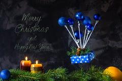 La tarjeta de la Navidad y del Año Nuevo con el texto y los juguetes azules le gusta un aire Foto de archivo libre de regalías