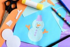La tarjeta de papel con applique del muñeco de nieve y el texto I aman invierno Tijeras, palillo del pegamento, lápiz, marcadores Fotografía de archivo