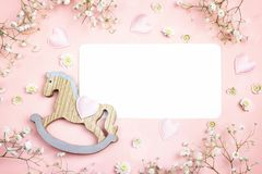 La tarjeta de papel en blanco con el mini juguete del caballo mecedora y el gypsophila fluyen Imágenes de archivo libres de regalías