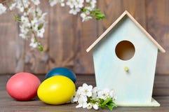La tarjeta de pascua con los huevos, la pajarera y la primavera de Pascua florece Fotos de archivo libres de regalías