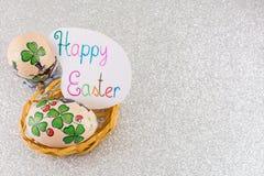 La tarjeta de pascua feliz con el trébol adornó los huevos de Pascua Fotos de archivo libres de regalías