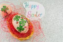 La tarjeta de pascua feliz con el trébol adornó los huevos de Pascua Fotografía de archivo