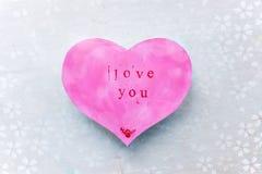 La tarjeta del día de tarjeta del día de San Valentín en la forma de un corazón rosado con la palabra le ama fotografía de archivo libre de regalías