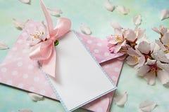 La tarjeta en blanco entre la almendra florece en fondo azul claro imagen de archivo