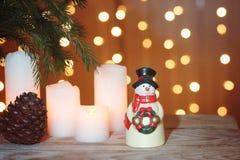 La tarjeta festiva con la guirnalda festiva, un muñeco de nieve se coloca en una tabla de madera Imagen de archivo