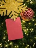 La tarjeta roja con el ornamento de la Navidad en pino verde sale del fondo Fotografía de archivo