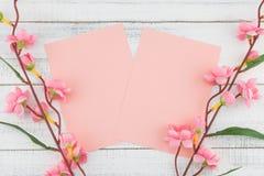 La tarjeta rosada en blanco adornada con la flor rosada falsa ramifica Imagenes de archivo