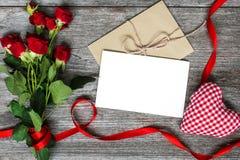 La tarjeta y el sobre blancos en blanco de felicitación con las rosas rojas florece Foto de archivo libre de regalías