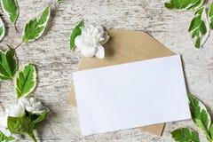 La tarjeta y el sobre en blanco de felicitación con el jazmín florece Fotografía de archivo