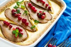 La tarta con las peras asadas sobre la crema del rikotta adornó los arándanos y las hojas de menta Foto de archivo