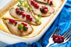 La tarta con las peras asadas sobre la crema del rikotta adornó los arándanos y las hojas de menta Imagenes de archivo