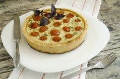 La tarta con los tomates, el queso y las cebollas de cereza en la placa blanca, cerca del cuchillo, bifurca Imagen de archivo libre de regalías