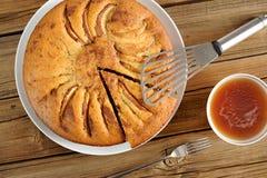 La tarte aux pommes faite maison a coupé avec la spatule, la fourchette et la tasse de thé Photographie stock libre de droits