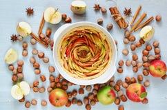 La tarte crue de pomme dans le plat de cuisson décoré des pommes coupées en tranches fraîches, noisettes, bâtons de cannelle, ani photo libre de droits