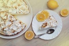 La tarte de citron avec la meringue a caramélisé la crème du plat sur le fond en bois blanc et un morceau de tarte avec des fruit Photographie stock