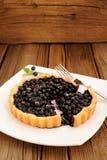 La tarte faite maison de myrtille a coupé dans le plat blanc carré avec la fourchette et Photographie stock