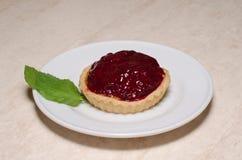 La tartelette ou le gâteau fraîche de baie a rempli de crème anglaise image libre de droits