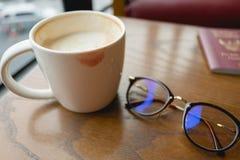 La tasse avec du café ont le baiser de rouge à lèvres sur la tasse et ont les verres p Photo stock