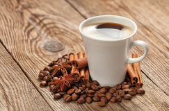 La tasse avec l'anis de grains de café et d'épices se tiennent le premier rôle Photo libre de droits