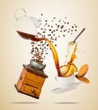 La tasse blanche de Porcelaine avec éclabousser le liquide de café, broyeur et biscuits, a séparé sur le fond brun photos stock