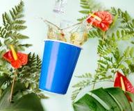 La tasse bleue avec le thé éclabousse sur le fond tropical des fleurs d'anthure de calla, de la fougère et des feuilles rouges de photos libres de droits