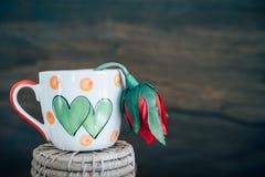 La tasse d'amour de vintage avec s'est levée sur le rétro fond Image stock