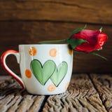 La tasse d'amour de vintage avec s'est levée sur le vieux fond en bois Photographie stock