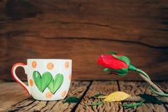 La tasse d'amour de vintage avec s'est levée sur le vieux fond en bois Image stock