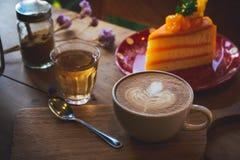 La tasse d'arome de café et le gâteau savoureux portent des fruits sur la table en bois dans le coff de café Images libres de droits