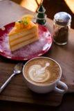 La tasse d'art de latte d'arome de café et le Noël savoureux durcissent sur le tabl en bois Image libre de droits