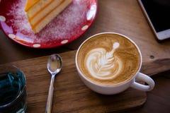 La tasse d'art de latte d'arome de café et le Noël savoureux durcissent sur le tabl en bois Photo libre de droits