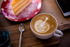 La tasse d'art de latte d'arome de café et le Noël savoureux durcissent sur le tabl en bois Photographie stock libre de droits