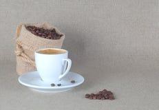 La tasse d'expresso avec des grains de café mettent en sac dessus de retour Photo libre de droits