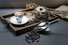 La tasse d'expresso, le grain de café, le livre et les fleurs sèches cognent sur en bois photographie stock libre de droits