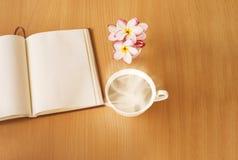 La tasse de boisson ou de café chaude avec le plumeria ou le frangipani fleurit I Photos stock